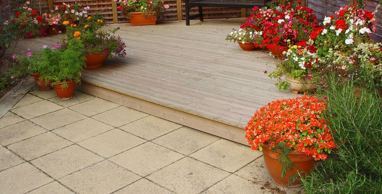 Stone patio with one step leading up to a deckin area with tubs of colourful flowers