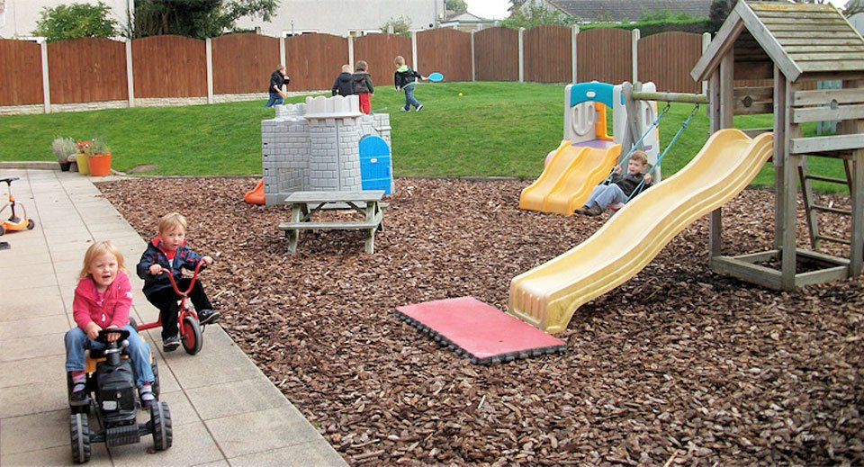 Children having fun on bikes and running around in the outdoor play area