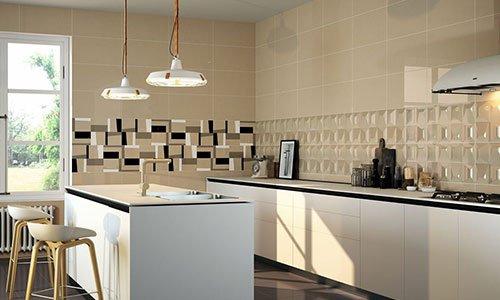 cucina moderna  con muri color beige e neri, penisola e mobili color panna, due lampade a sospensione , lavandino sulla penisola e due sedie sgabelli con gambe in legno di color marrone e beige
