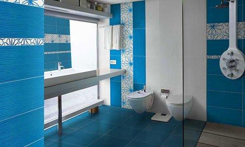bagno con piastrelle blu e bianche a fiori, sulla sinistra un lavandino con uno specchio, al centro il bidet e il wc e sulla destra un vetro che divide la doccia dal resto della stanza