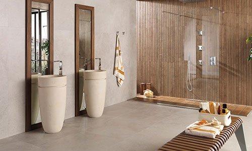 stanza con soffitto in legno, una vetrata con dietro una doccia a soffitto molto moderna due lavandini a forma ovale di color bianco uno a distanza dall'altro e una panca in legno con sopra una scatola bianca con dei prodotti