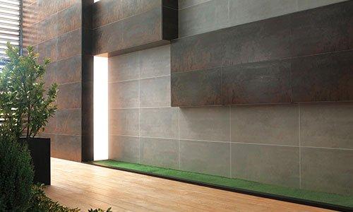 un muro di color marrone e grigio a effetto tridimensionale e vicino dei vasi con delle piante e una striscia di prato artificiale