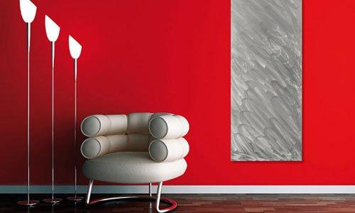 stanza con muri di color rosso, un quadro  dipinto in grigio, tre lampade con base in acciaio e una poltrona in pelle beige con schienale doppio