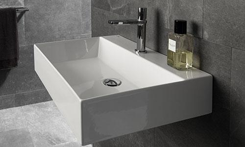 un lavabo a forma quadrata di color bianco con rubinetto in acciaio si intravede uno specchio e un portasciugamani con un asciugamano marrone