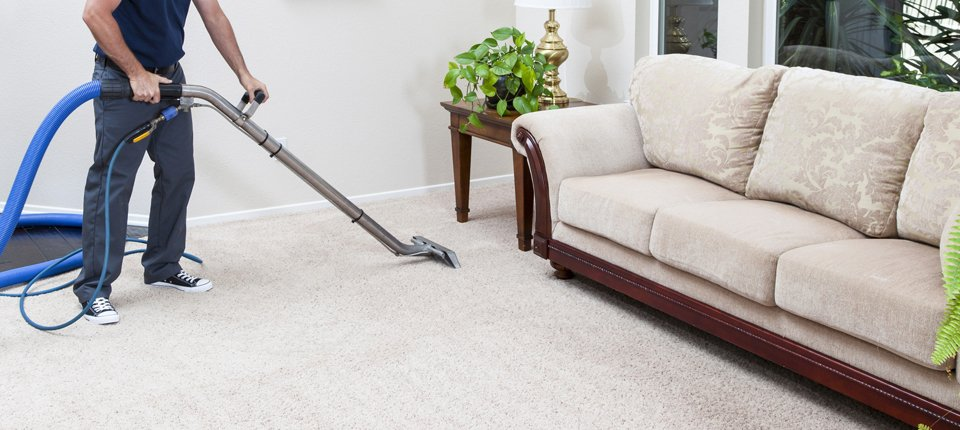 A man deep cleaning a thick pile cream carpet