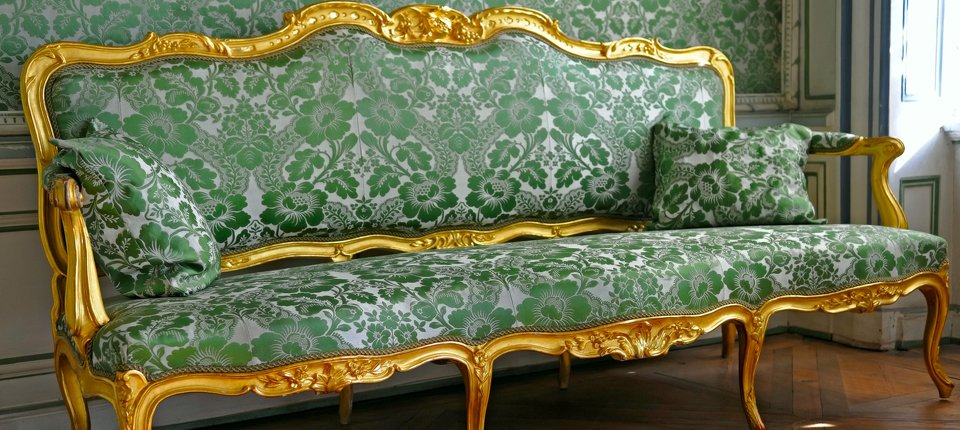 A grand sofa with golden frame and stylish green upholstery