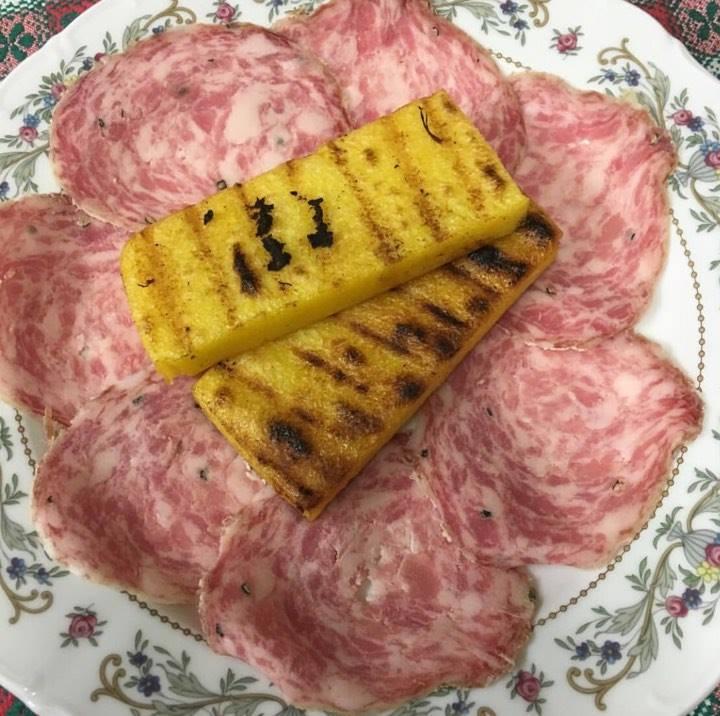 Polenta servita sun un piatto di salumi