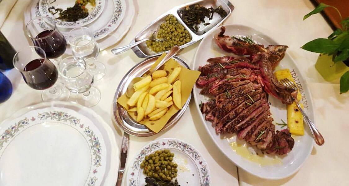Tavola imbandita con taglaita fiorentina, patate al forno e piselli