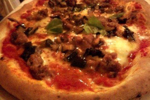 Pizza rossa con salciccia e funghi