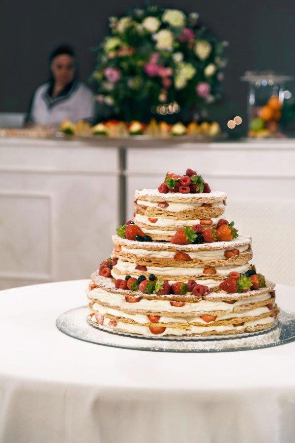 una torta a più livelli con panna, fragole e frutti di bosco