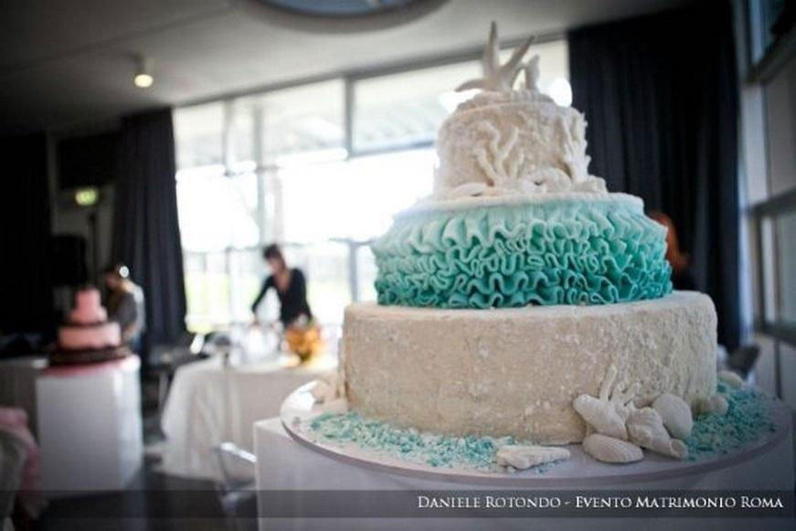 una torta a tre piani di color bianco e verde smeraldo con delle stelle marine
