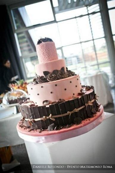 una torta a più livelli di color rosa con del cioccolato