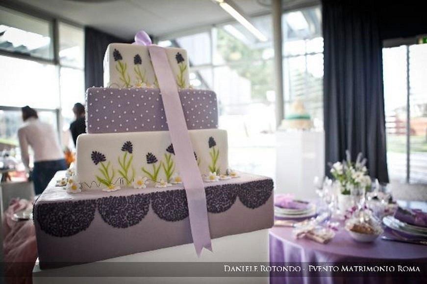 una torta a 4 piani a forma di pacchetti regalo con un nastro