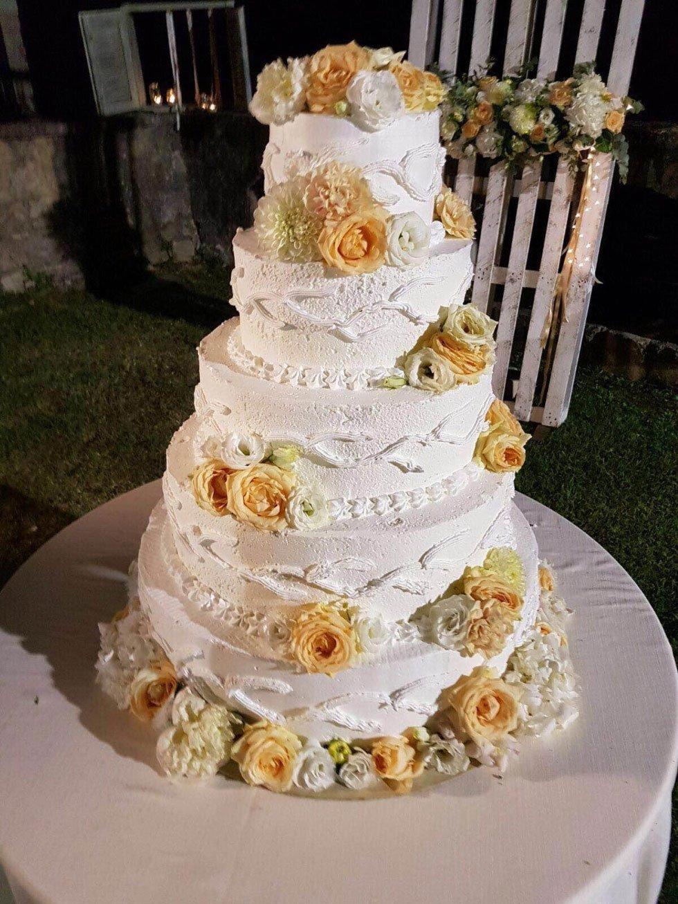 una torta a più livelli con panna e delle rose bianche e arancioni