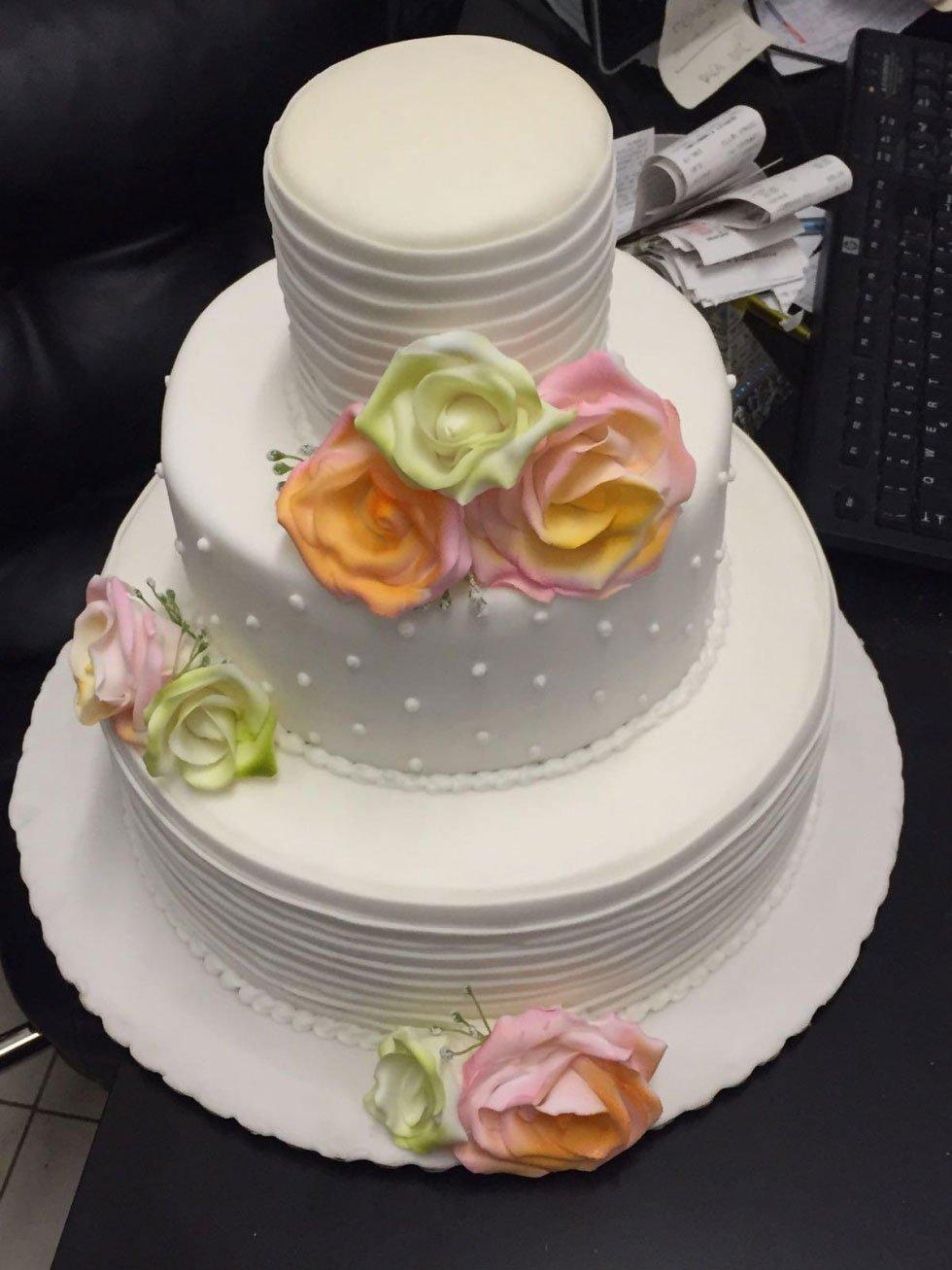 tre una torta bianca a tre piani con dei fiori colorati
