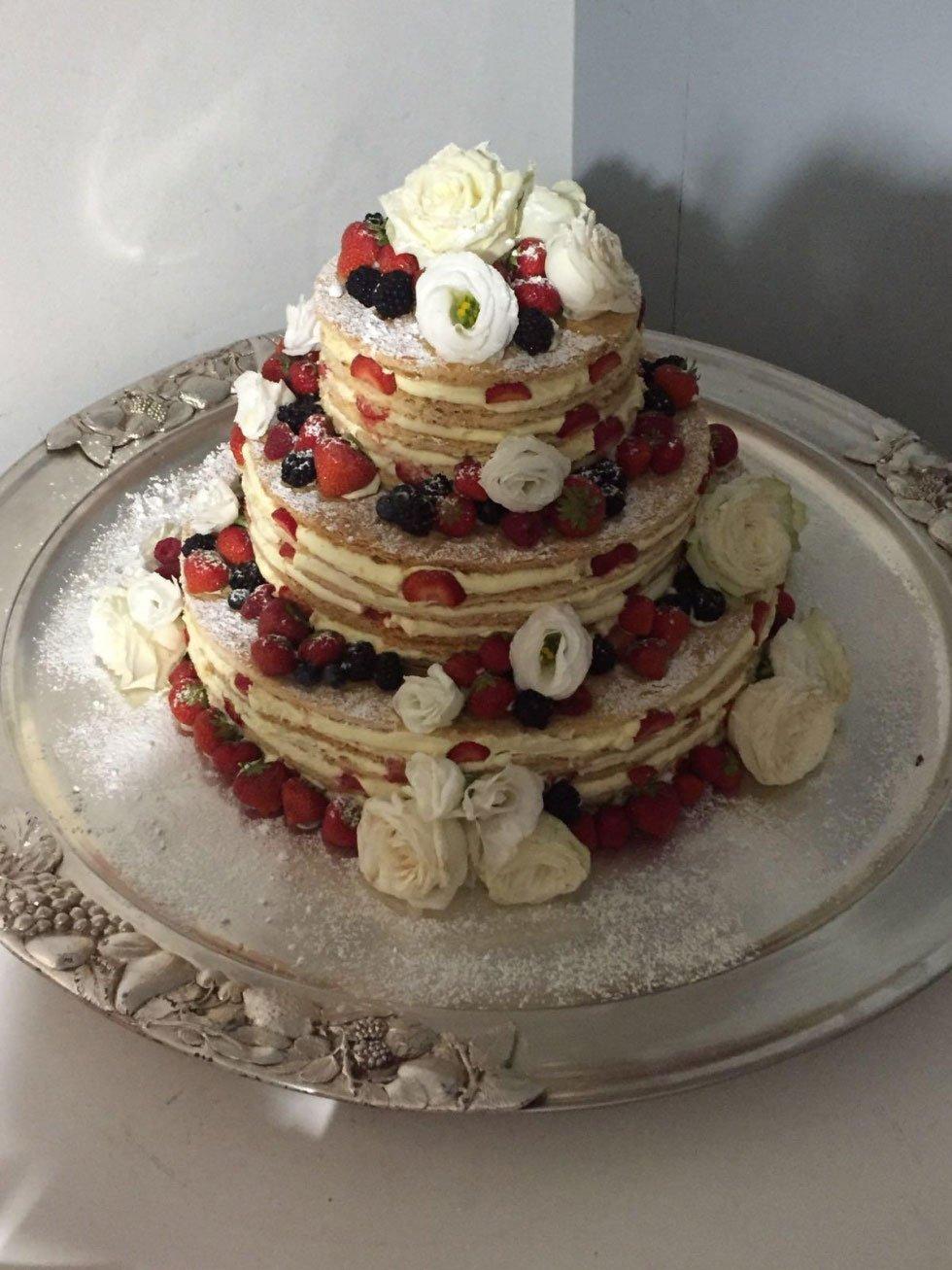 una torta a più livelli con crema pasticcera, frutti di bosco zucchero a velo e delle rose bianche