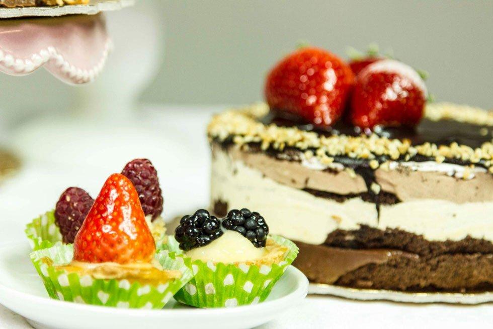 dei pasticcini alla frutta e una torta al cioccolato con sopra una fragola