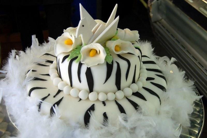 una torta zebrata con una collana di perle bianca e sopra un cigno con dei fiori