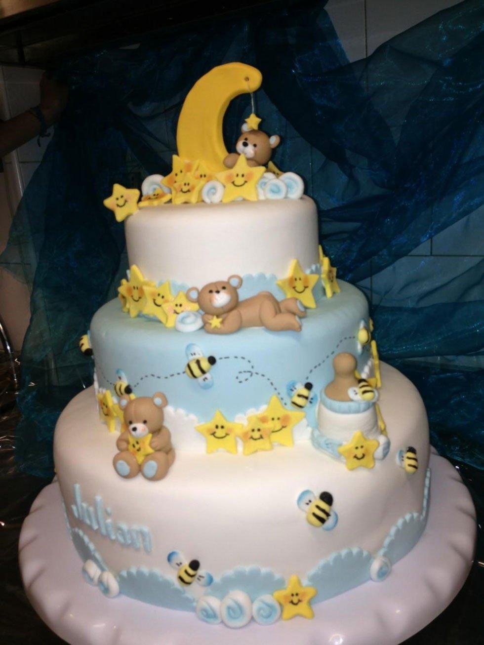 una torta a più livelli con con una glassa bianca e azzurra e degli orsetti e delle stelline