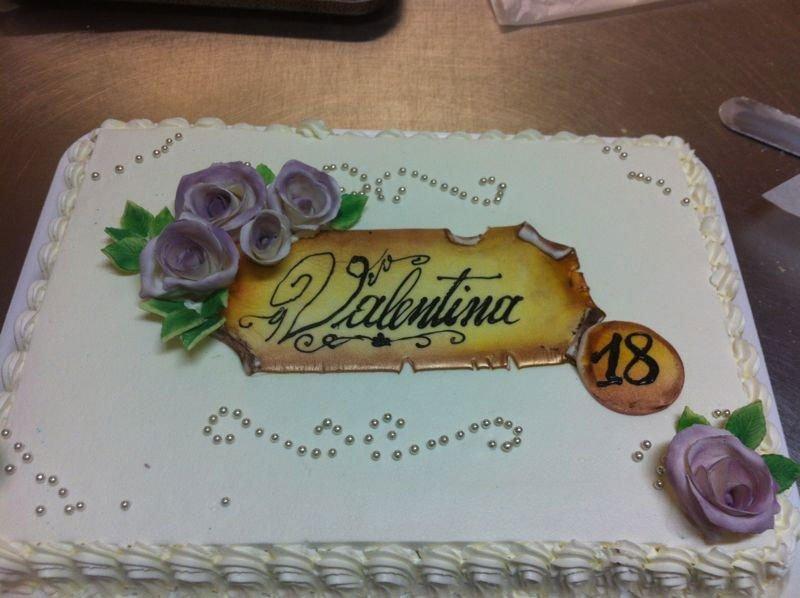 una torta rettangolare di color bianco con dei fiori viola e la scritta Valentina 18