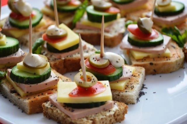 delle fettine di pane con prosciutto,zucchine,formaggio e olive