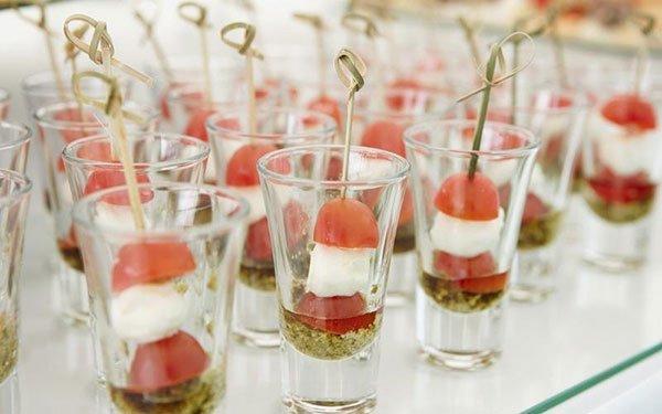 dei bicchieri con dentro degli stuzzichini di mozzarella e pomodoro