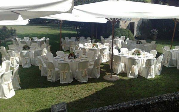 dei tavoli apparecchiati per un ricevimento sotto delle tende all'esterno