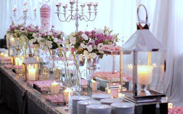 una tavolata con dei candelabri, lumini rosa,piatti e vasi di fiori