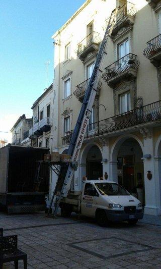 vista di un camioncino bianco con una scala estendibile con una piattaforma per traslochi in una casa in città