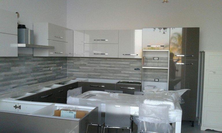 una cucina moderna color bianco e grigio con al centro un tavolo bianco e delle sedie con ancora su la plastica