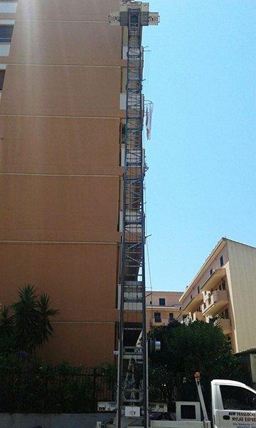 una scala estendibile con sopra una piattaforma per traslochi vista da un viale della città con degli alberi e dei palazzi bianchi