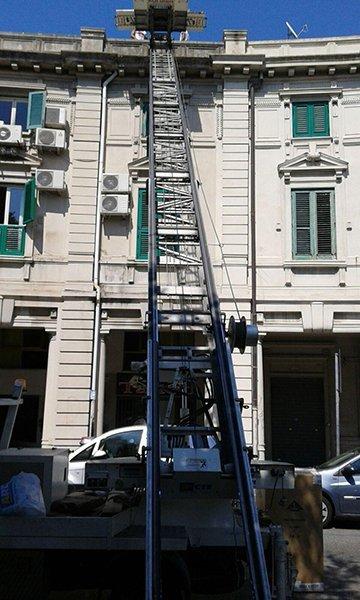 una scala con una piattaforma in uno stabile in città e sotto delle macchine parcheggiate