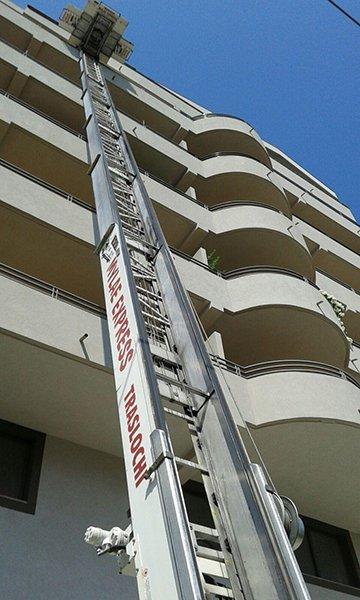 visa di una lunga scala estendibile con una piattaforma vicino a uno stabile di color bianco con vista dei balconi
