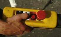 un dito che preme su un telecomando giallo con un grande pulsante rosso