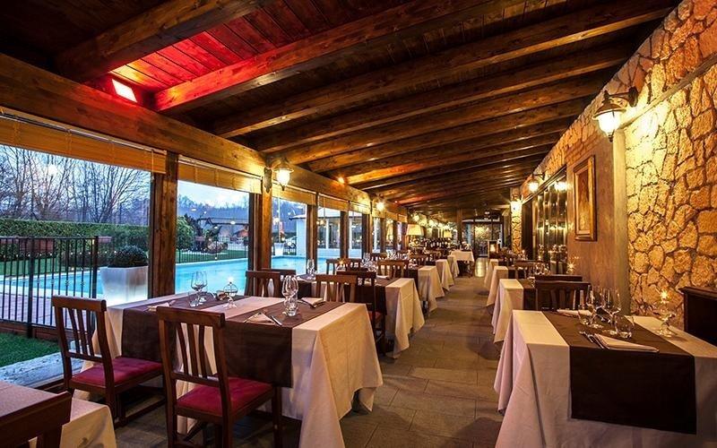 vista laterale di un ristorante con soffitto in legno,apparecchiati, infissi esterni in vetri e piscina