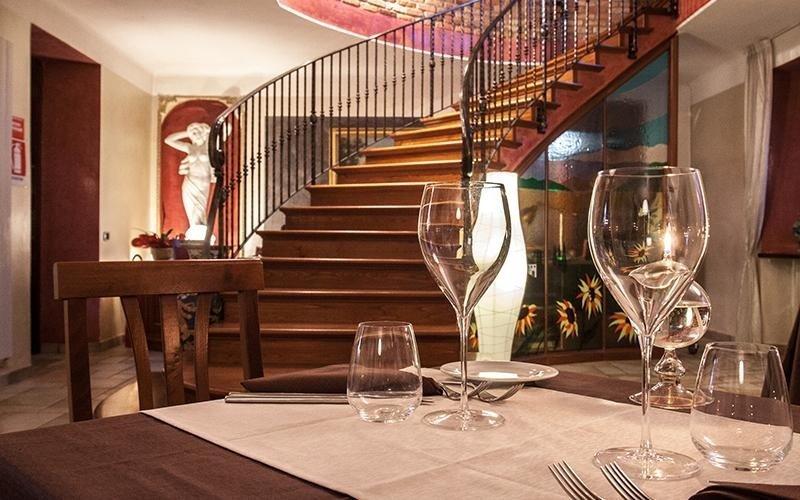 tavolo apparecchiato con bicchieri e una scala interna in legno