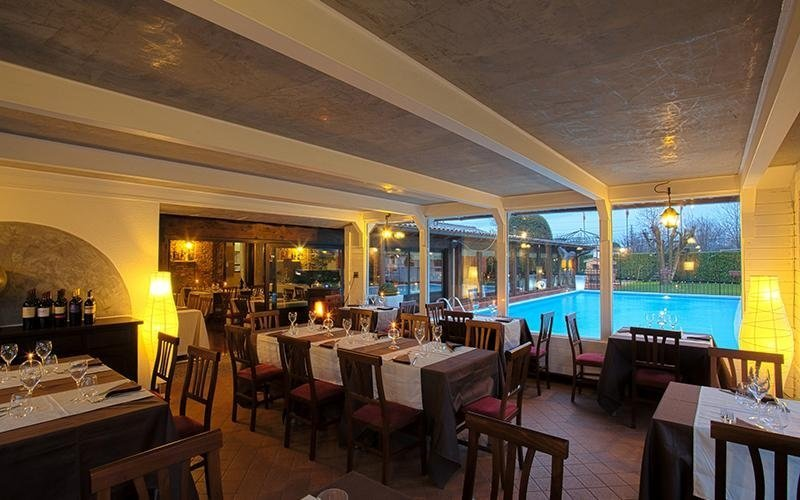 piscina vista da un ristorante con tavoli apparecchiati, infissi esterni in vetro e lampadine