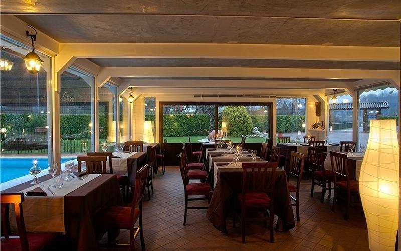 vista interna di un ristorante con tavoli apparecchiati, infissi esterni in vetro e lampadine