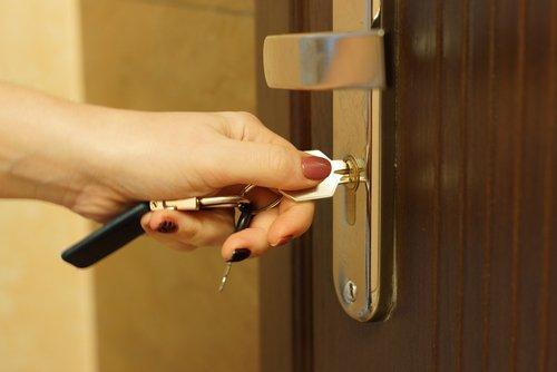 mano che aptre una porta con una chiave