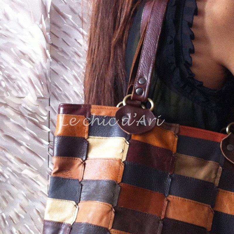 vista ravvicinata di una borsa di pelle con patchwork di pelle di color nero, marrone, bordeaux e bianco