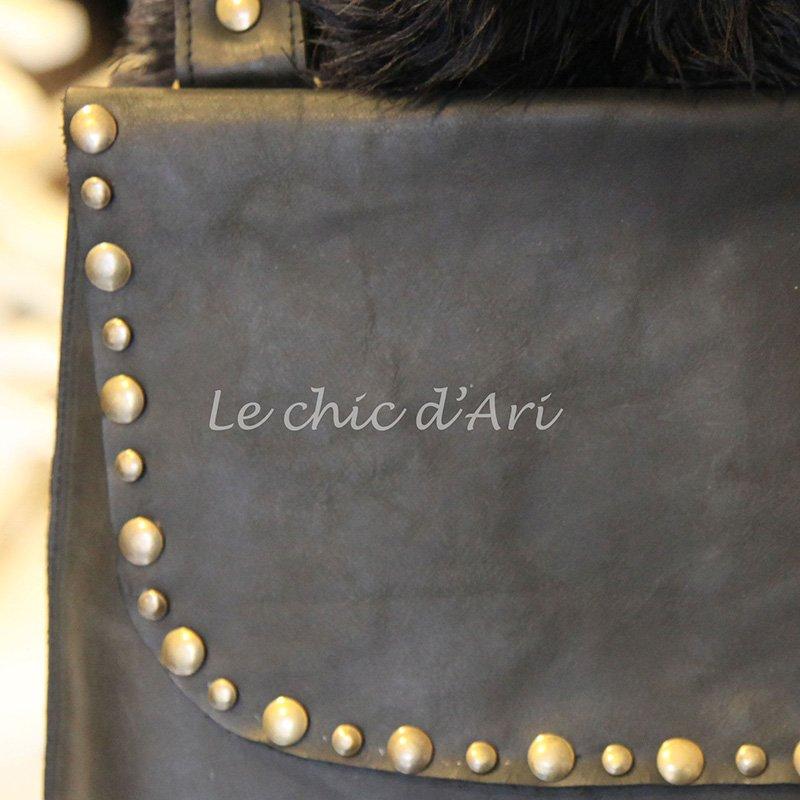 Una borsetta di pelle con dei bottoni dorati