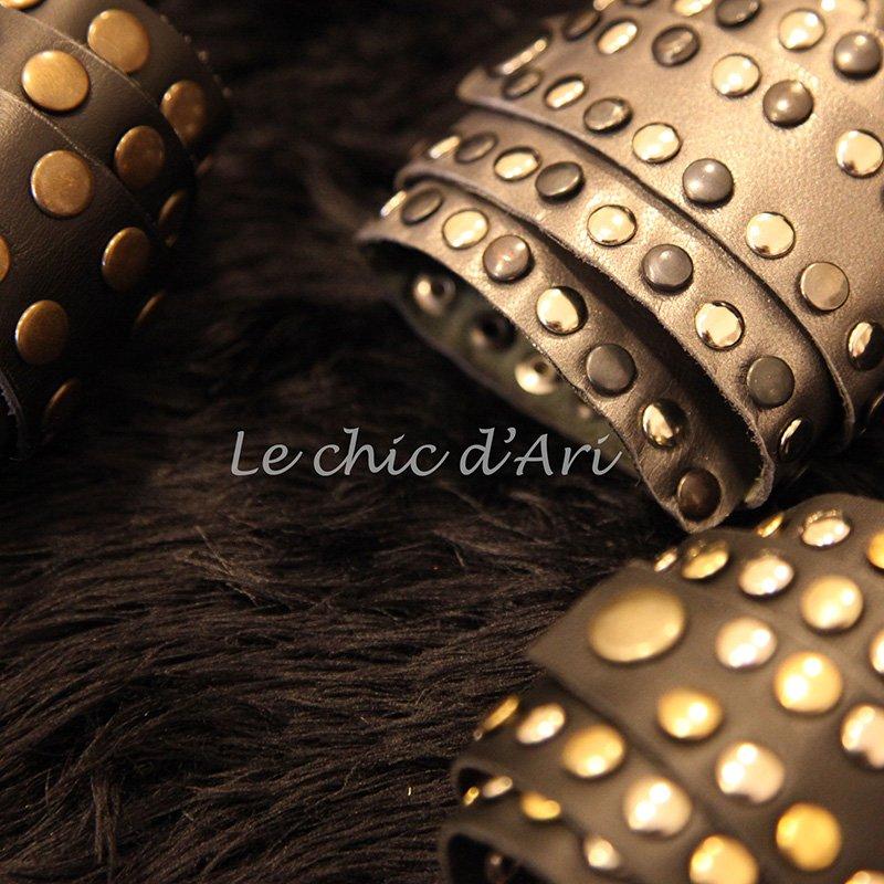 Dei braccialetti di pelle con bottoni dorati