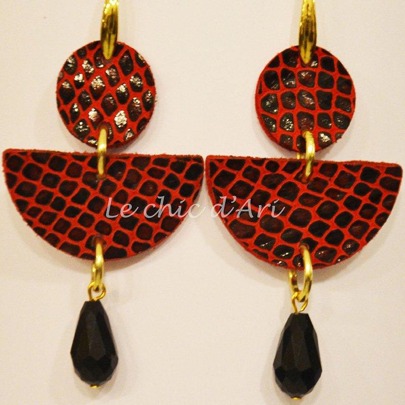 Degli orecchini di pelle di color rosso e nero con anelli dorati