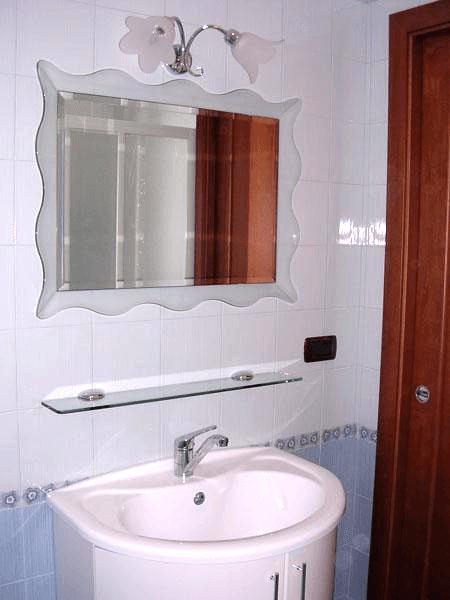 Specchio con cornice inclinata e ondulata