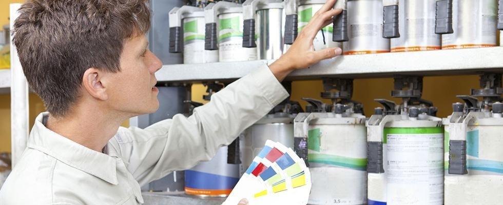 un uomo sta cercando un particolare colore di vernice da uno vasto assortimento