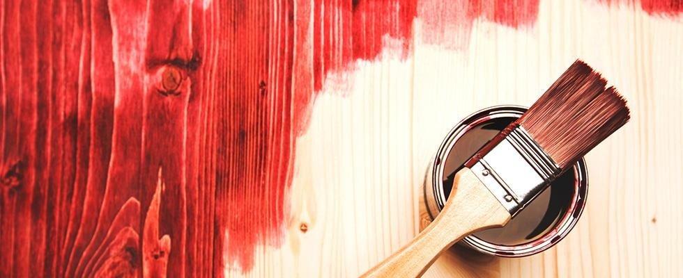 barattolo di vernice con pennello appoggiato sopra e muro verniciato