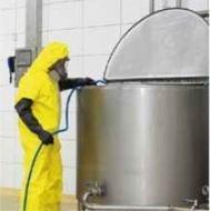 uomo con tuta e maschera integrale inserisce un tubo in una cisterna