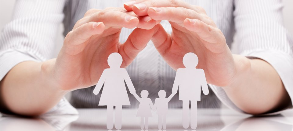 Cupped hands above a paper cutout of a family of four