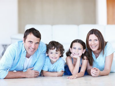 A young family of four, all wearing pale blue tops, sitting in a row at a table