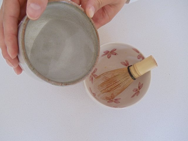 Warm up tea whisk and cup with hot water and then dry cup